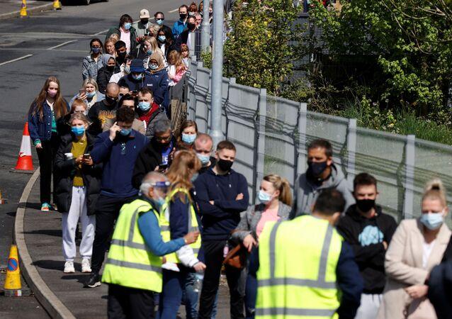 Fila de pessoas para receber vacina na cidade de Bolton, no Reino Unido