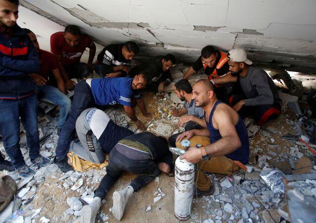 Palestinos atuam para retirar pessoas de escombros de prédio bombardeado por Israel na Faixa de Gaza