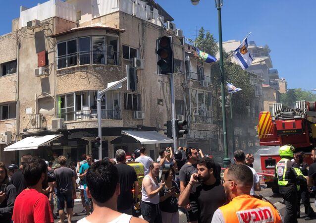 Pedestres e socorristas se reúnem em local atingido por foguete disparado de Gaza, em Ramat Gan, distrito de Tel Aviv, Israel, 15 de maio de 2021