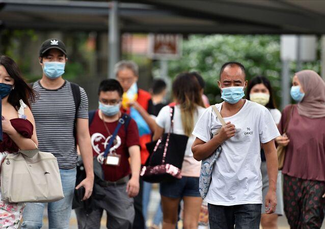 Pessoas usando máscaras de proteção atravessam uma estrada em Cingapura, 14 de maio de 2021