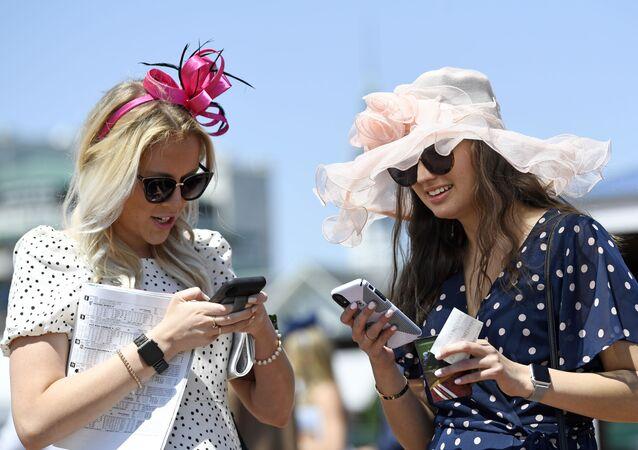 Mulheres usam seus celulares, EUA, 1 de maio de 2021