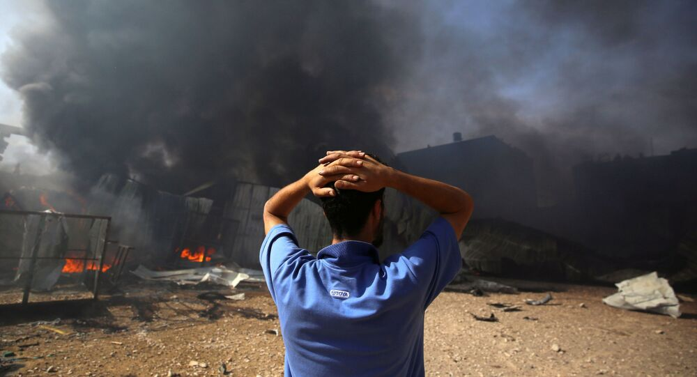 Homem coloca a mão na cabeça após fábrica ser bombardeada por forças israelenses, no norte da Faixa de Gaza, 17 de maio de 2021