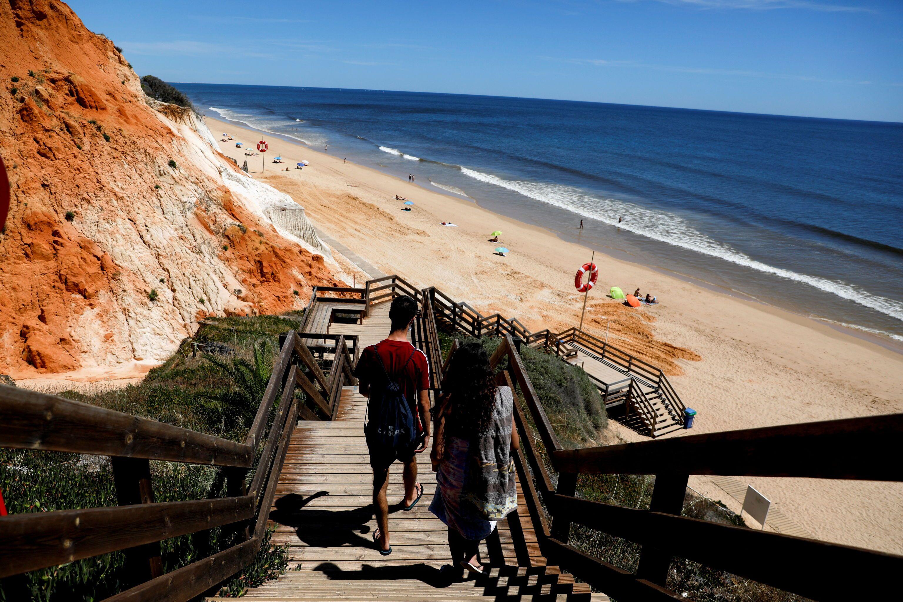 Pessoas descendo para praia da Falésia no primeiro dia de reabertura de fronteiras de Portugal para turistas do Reino Unido, Albufeira, Portugal, 17 de maio de 2021