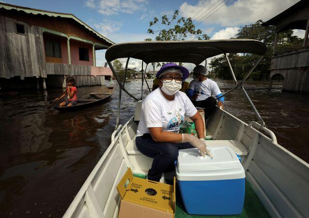 Funcionária de saúde transporte em barco, pelo rio Solimões, doses da vacina de Oxford/AstraZeneca contra o coronavírus
