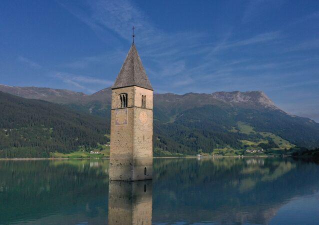 Vista aérea mostra o campanário de uma igreja submergida no lago Resia, no norte da Itália