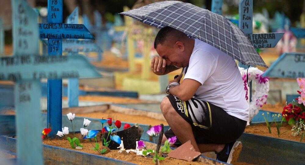 Homem chora ao lado de túmulo de parente vítima da COVID-19, em Manaus, 9 de maio de 2021