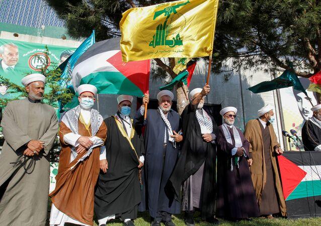 Líderes religiosos empunham bandeiras do Hezbollah e da Palestina em Kfar Kila, Líbano, 14 de maio de 2021