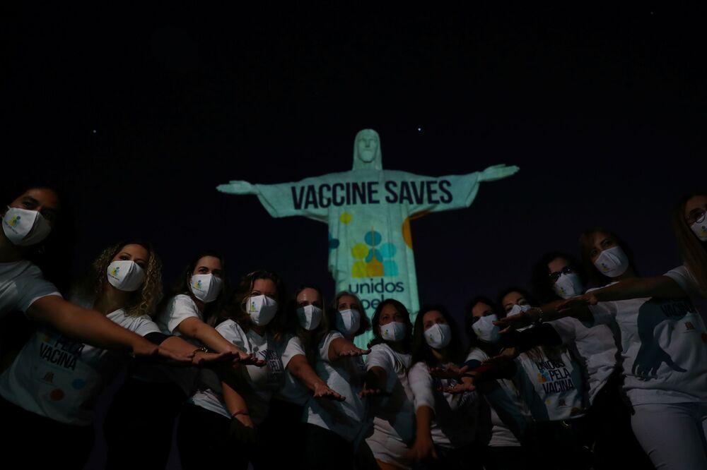 Membros do Movimento Unidos da Vacina em frente à estátua do Cristo Redentor com uma mensagem em inglês Vacina salva, a fim de sensibilizar a população para a importância da vacina contra coronavírus, 15 de maio de 2021