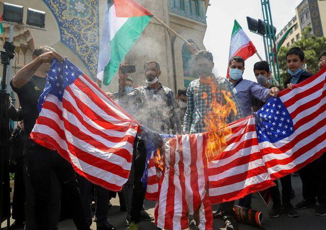 Iranianos queimam bandeiras dos EUA durante protesto para expressar solidariedade ao povo palestino, em Teerã, Irã, em 18 de maio de 2021