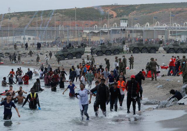 Cidadãos marroquinos caminham na água enquanto legionários espanhóis patrulham a área perto da cerca em uma praia em El Tarajal,  em Ceuta, Espanha, 18 de maio de 2021