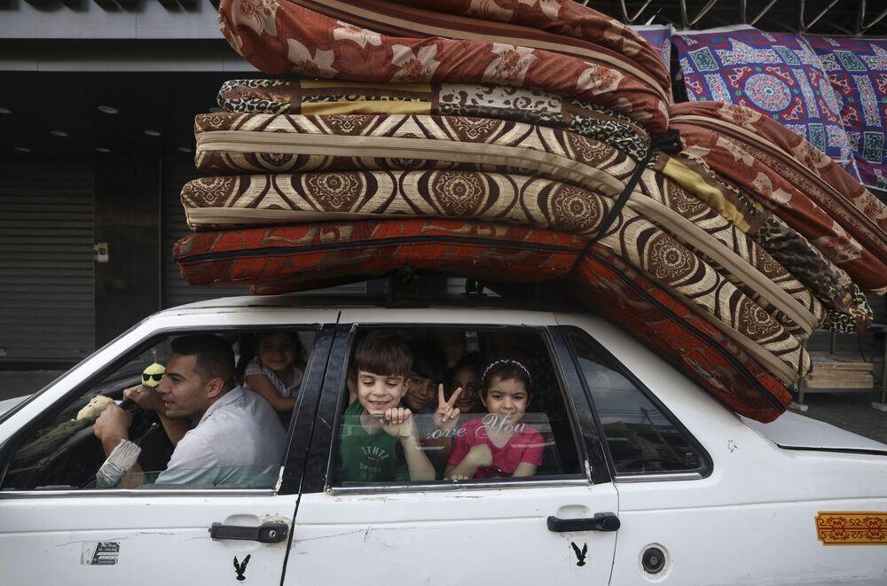Família palestina volta para casa na Cidade de Gaza, após cessar-fogo ter sido acordado entre Israel e o Hamas, 21 de maio de 2021