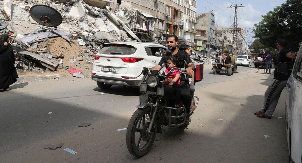 Palestinos passam de moto por área atingida por ataque aéreo israelense, Faixa de Gaza, 21 de maio de 2021