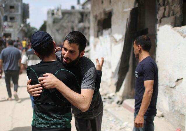 Palestinos se abraçam ao voltarem para suas casas destruídas após o cessar-fogo entre Israel e o Hamas, no noroeste de Faixa de Gaza, 21 de maio de 2021