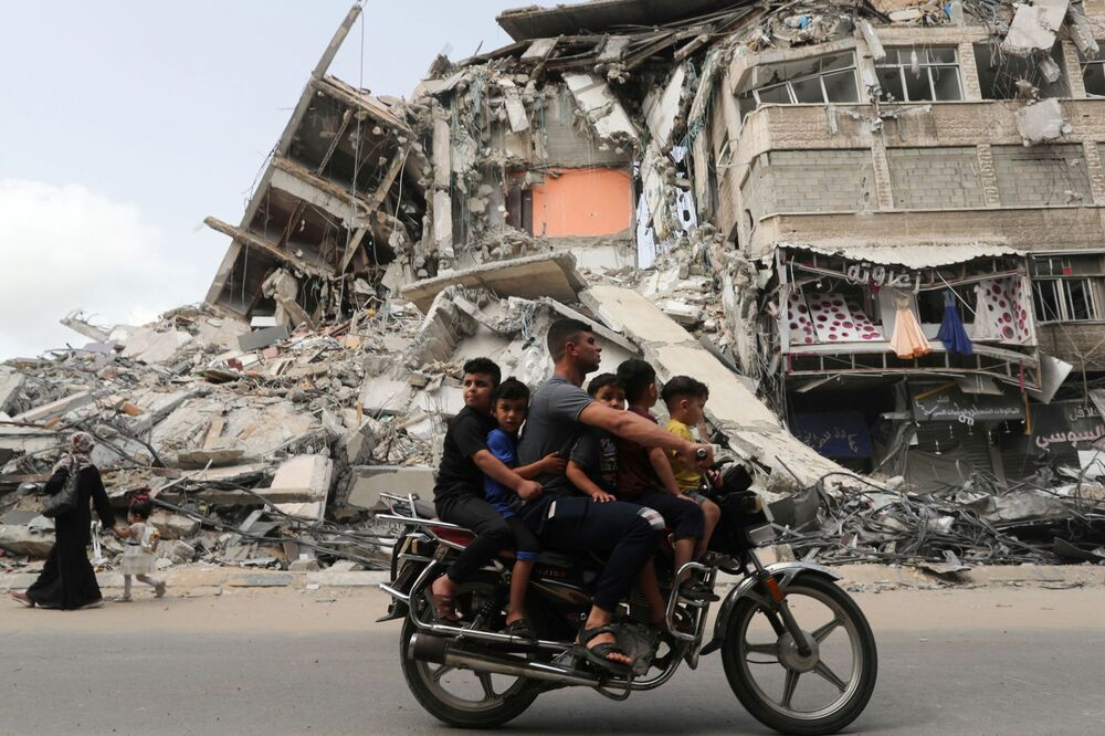 Palestinos passam de moto por local que sofreu um ataque aéreo israelense, 21 de maio de 2021