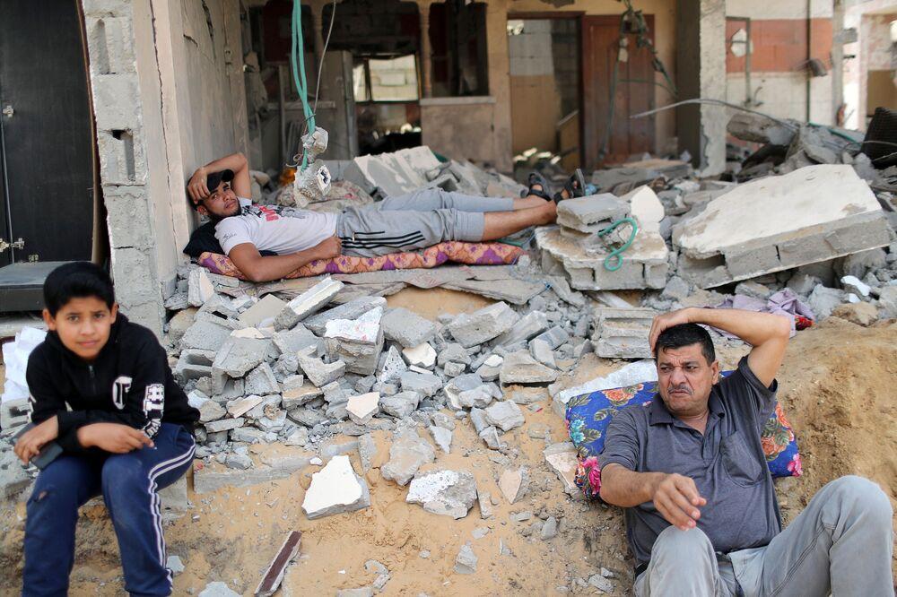 Palestinos descansando após terem voltado para suas casas na cidade de Beit Hanoun, Faixa de Gaza, 21 de maio de 2021