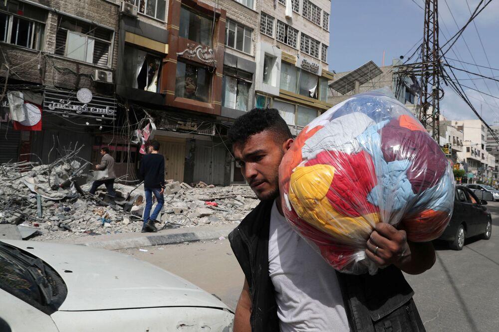 Palestino passando ao lado das ruínas geradas por ataque aéreo israelense durante o conflito entre o Hamas e Israel, Faixa de Gaza, 21 de maio de 2021