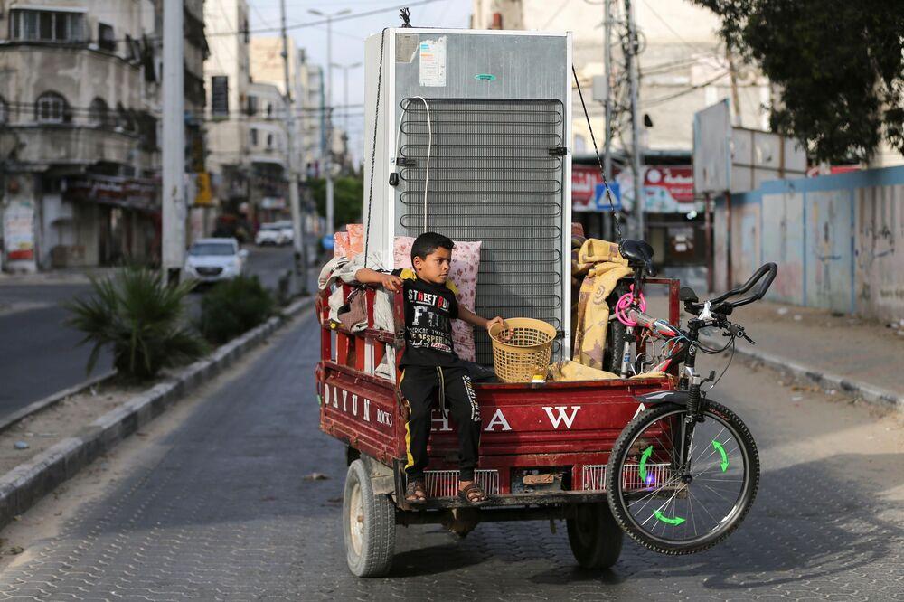 Menino palestino em um riquixá carregado com pertences de sua família rumo a sua casa, Faixa de Gaza, 21 de maio de 2021
