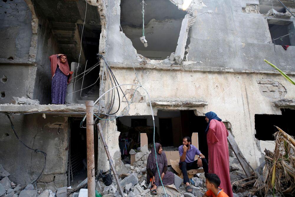 Palestinos sentam-se sobre os escombros de prédio destruído após o cessar-fogo no conflito entre Israel e o Hamas, Faixa de Gaza, 21 de maio de 2021