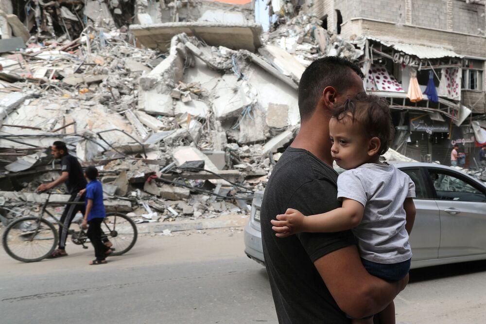 Palestino segura criança enquanto passa perto das ruínas de um prédio destruído pelo ataque aéreo israelense no conflito recente entre Israel e o Hamas, 21 de maio de 2021