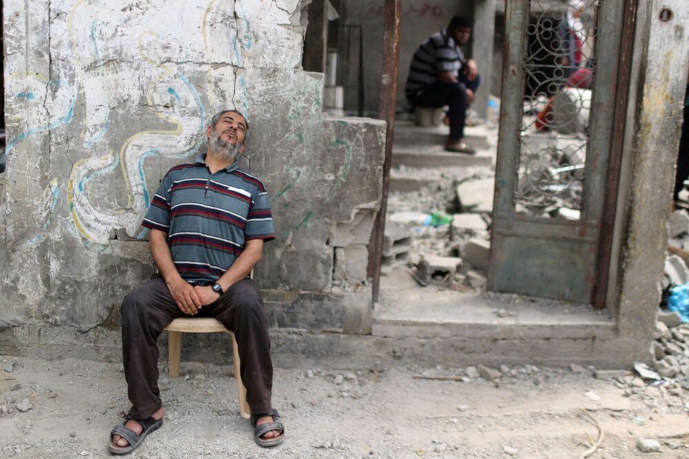 Palestino descansa após voltar a sua casa danificada depois do cessar-fogo declarado entre Israel e o Hamas, na cidade de Beit Hanoun, Faixa de Gaza, 21 de maio de 2021
