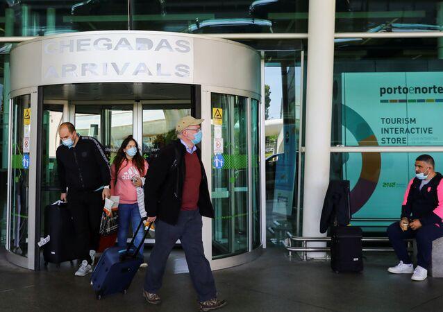 Viajantes saem do Aeroporto do Porto no primeiro dia em que turistas britânicos foram permitidos a entrar em Portugal, 17 de maio de 2021