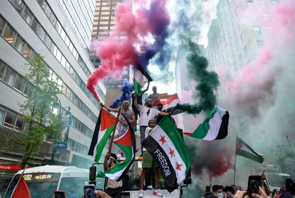 Manifestantes seguram bandeiras palestinas e sírias em apoio à Palestina no conflito com Israel, Nova York, EUA
