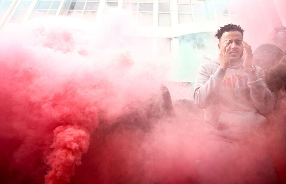 Manifestante palestino rodeado de fumaça vermelha durante protesto em Londres, Reino Unido, 15 de maio de 2021
