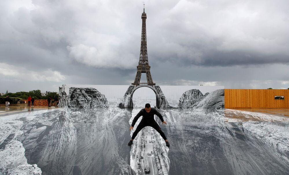 Homem posa na frente de obra gigante do artista francês JR na Praça Trocadéro, junto à Torre Eiffel, Paris, 19 de maio de 2021