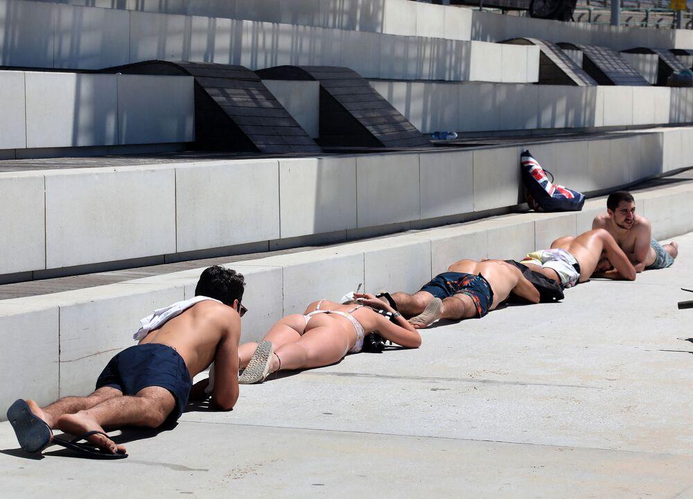 Cidadãos em Tel Aviv tomam banhos de sol, após lançamentos de foguetes a partir da Faixa de Gaza, 15 de maio de 2021