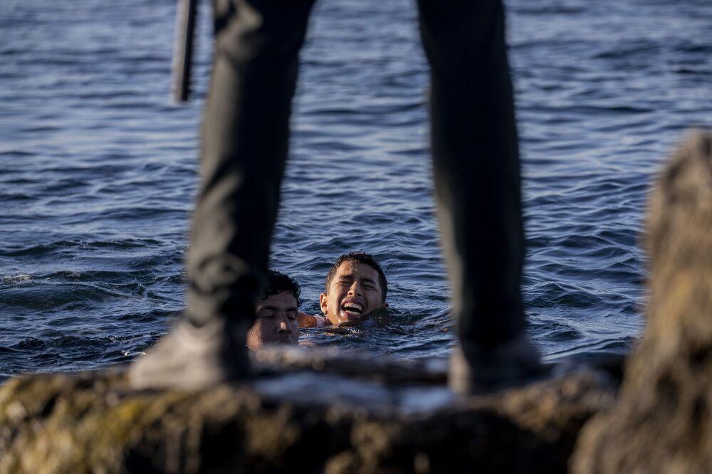 Agente da Guarda Civil da Espanha observa migrantes na costa do enclave espanhol de Ceuta, no norte de África, perto da fronteira entre Marrocos e Espanha, 19 de maio de 2021