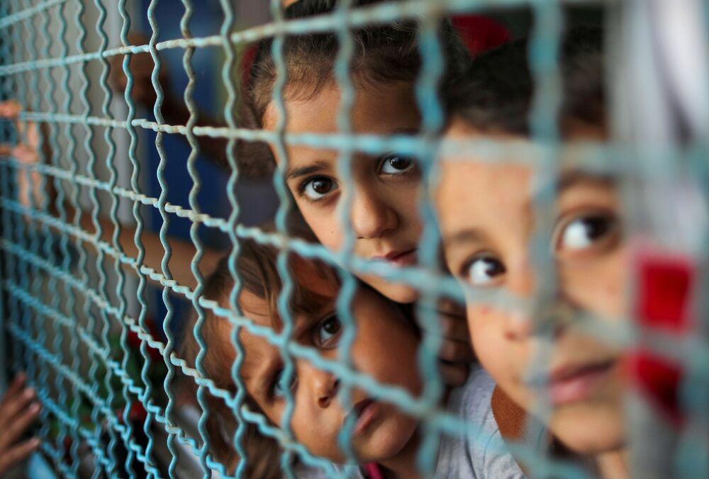 Crianças palestinas, que abandonaram suas casas por causa dos ataques aéreos e de artilharia de Israel, olham através da cerca da escola sob gerência da ONU, Faixa de Gaza, 18 de maio de 2021