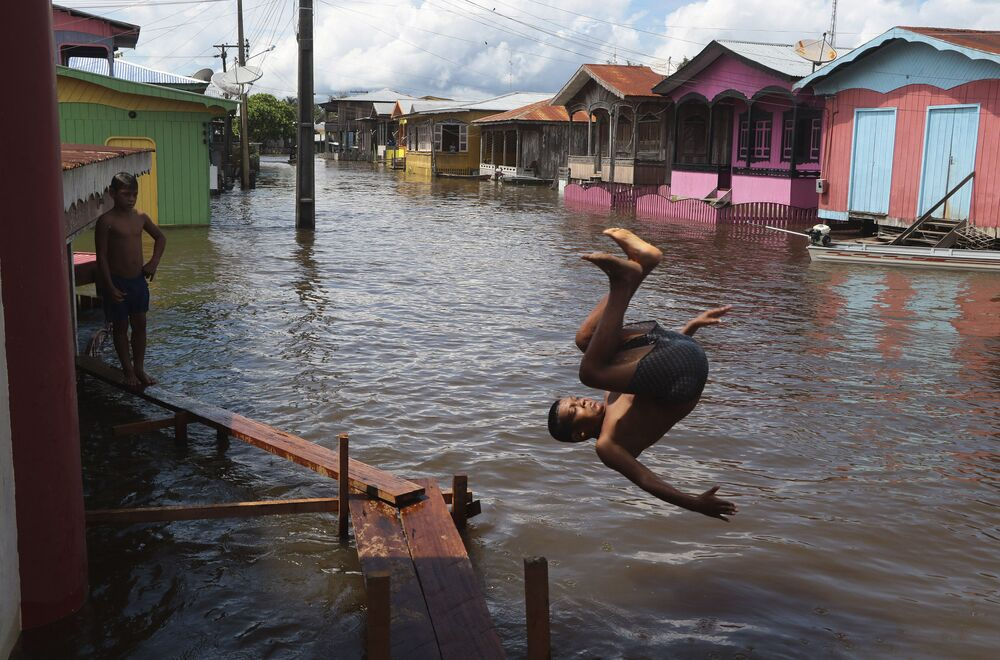 Menino salta para a água em rua inundada no estado do Amazonas, Brasil