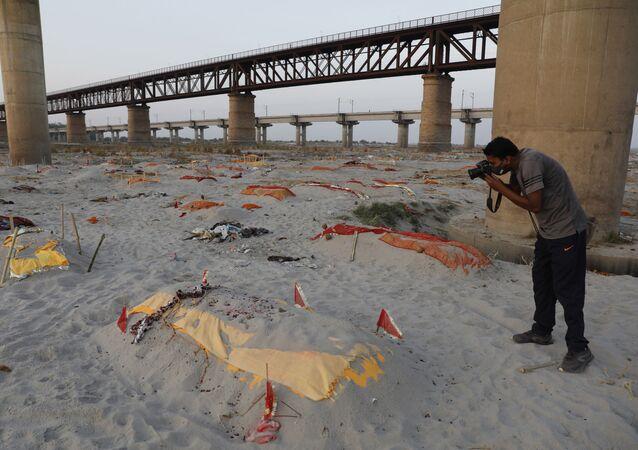 Corpos de supostas vítimas da COVID-19 enterrados na areia perto de um local de cremação nas margens do rio Ganges, em Prayagraj, Índia, em 15 de maio de 2021