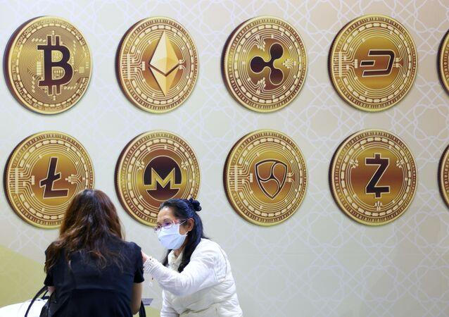 Clientes falam junto a painel com símbolos de criptomoedas durante a Expo Financeira Internacional de Taipé 2020, em Taipé, Taiwan, 27 de novembro de 2020