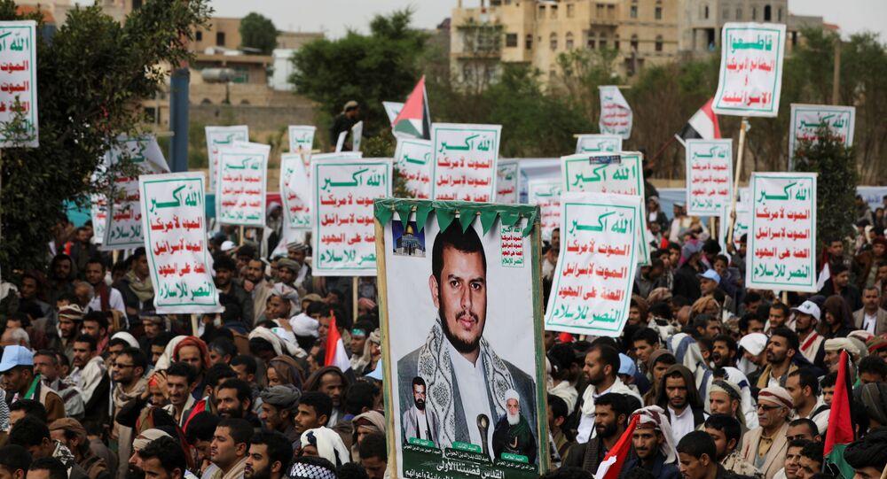 Apoiadores do movimento houthi seguram cartaz de Abdul-Malik al-Houthi, líder do movimento, durante ação pró-palestina em Sanaã, Iêmen, 7 de maio de 2021