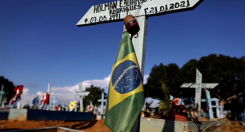 Bandeira do Brasil pendurada em cruz em túmulo de vítima do coronavírus, no cemitério Parque Taruma, em Manaus (AM)