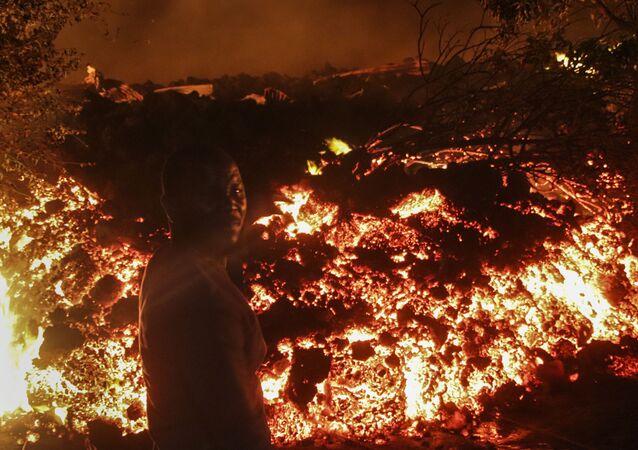 Uma pessoa fica em frente à lava da erupção do monte Nyiragongo, em Buhene, nos arredores de Goma, no Congo, na madrugada de domingo, 23 de maio de 2021