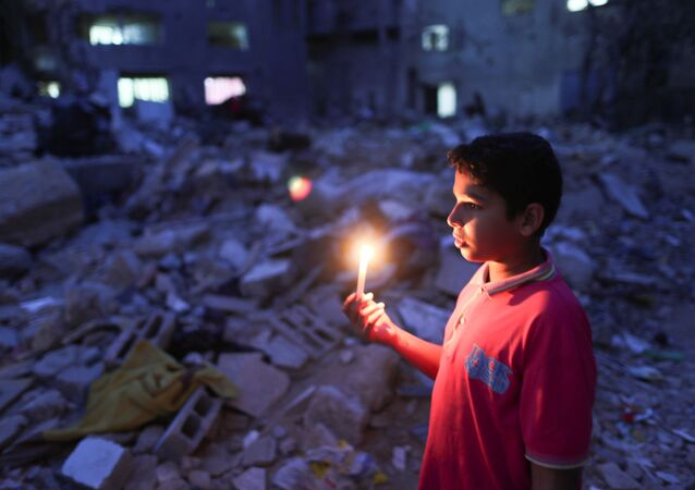 Menino segura vela no local onde uma casa foi destruída por ataques aéreos israelenses, em Gaza em 23 de maio de 2021