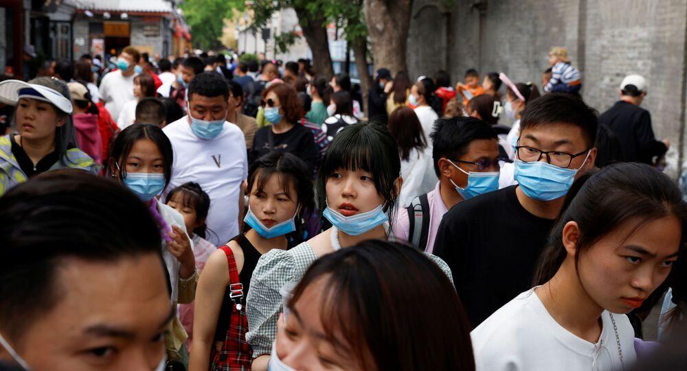 Pessoas andam com máscaras de proteção em Pequim, China, 4 de maio de 2021
