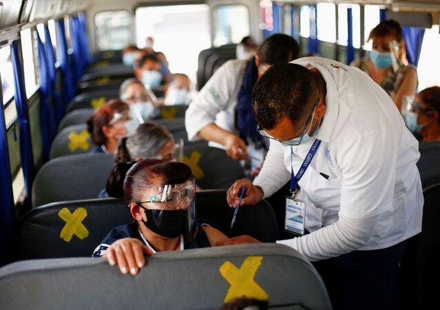 Em Juarez, no México, operários de uma fábrica recebem doses da vacina da Pfizer/BioNTech contra a COVID-19, em 24 de maio de 2021