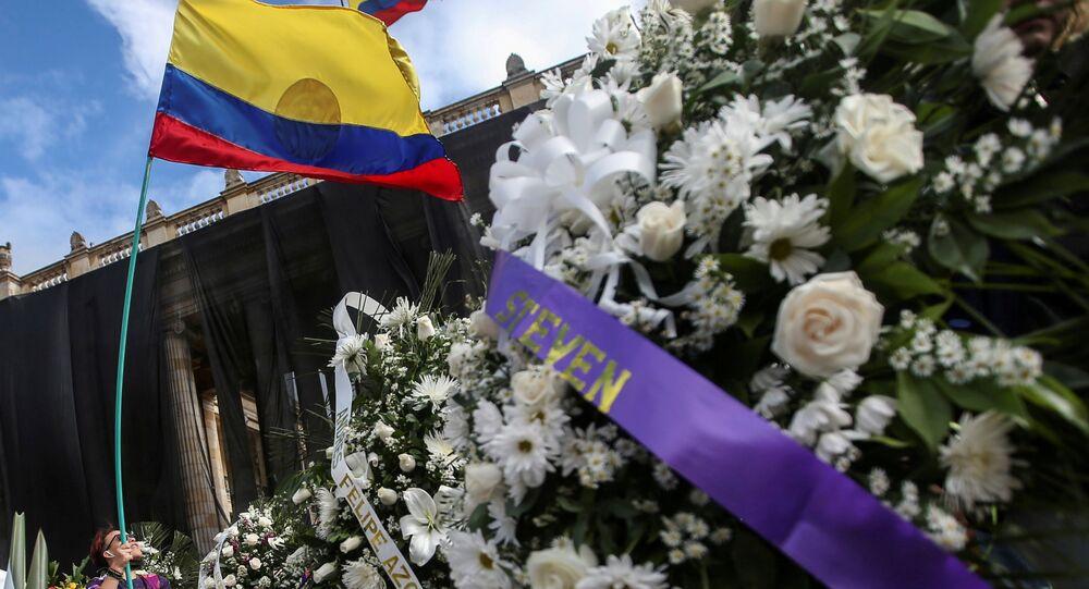 Manifestante ergue bandeira colombiana perto de coroas de flores com nomes de pessoas que morreram em protestos recentes, em Bogotá, Colômbia, 24 de maio de 2021