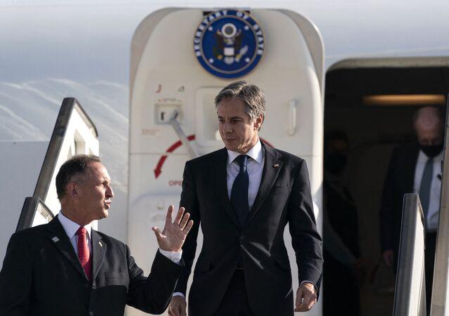 Secretário de Estado dos EUA, Antony Blinken (ao centro) é recebido pelo chefe de protocolo de Estado de Israel, Gil Haskelas, ao desembarcar em Tel Aviv, 25 de maio de 2021