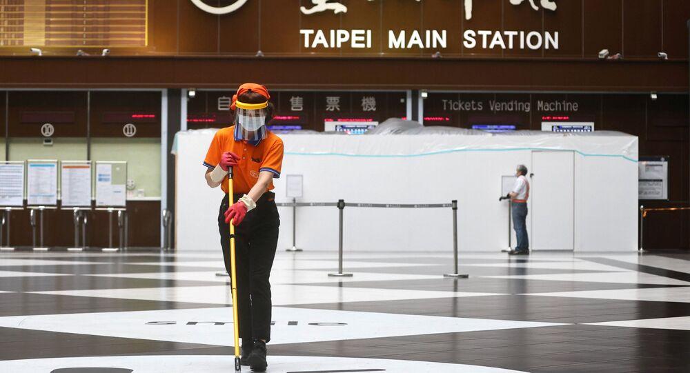 Mulher usa viseira e máscara na estação ferroviária principal de Taipé em meio à propagação da doença do coronavírus (COVID-19), em Taipé, Taiwan, 18 de maio de 2021