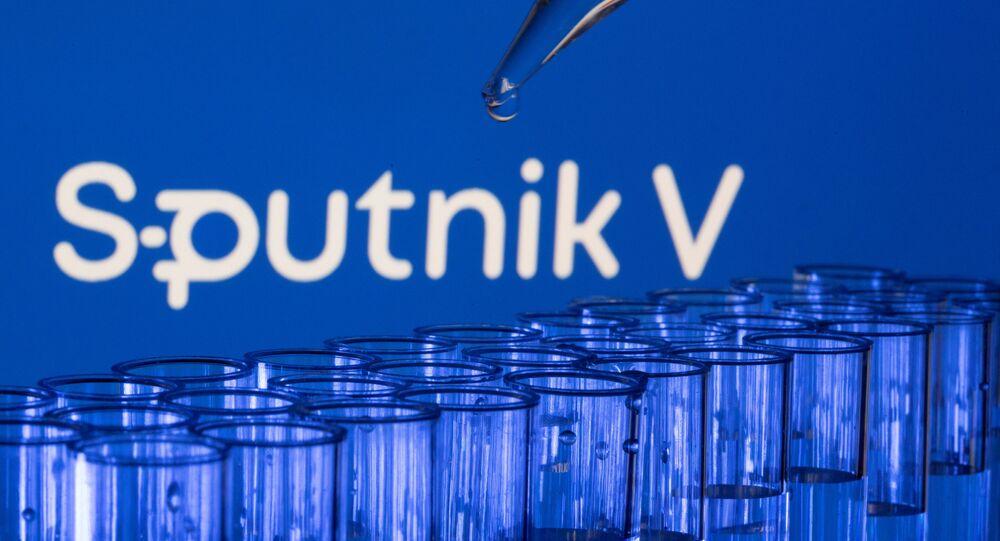 Tubos de ensaio são vistos à frente de um logotipo do Sputnik V, em foto de 21 de maio de 2021