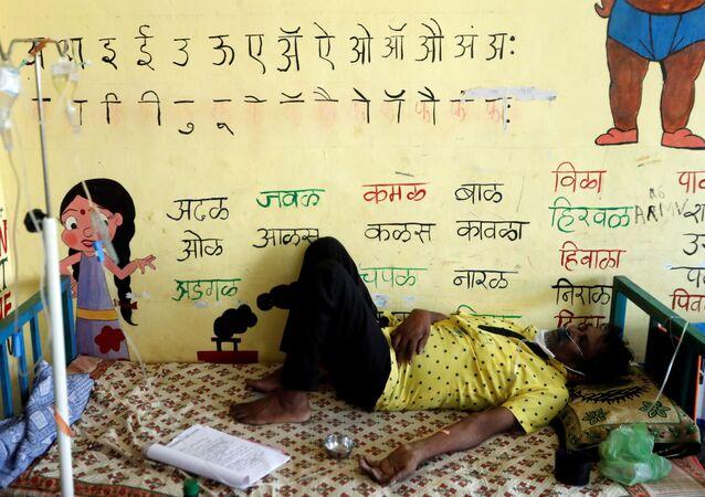Homem doente recebe suporte de oxigênio em uma escola transformada em unidade de atendimento da COVID-19 nos arredores de Mumbai, Índia, 24 de maio de 2021