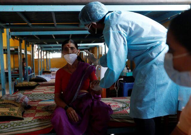 Um médico inspeciona um paciente com COVID-19 em uma sala de aula transformada em instalação de cuidados contra a pandemia nos arredores de Mumbai, na Índia, em 24 de maio de 2021