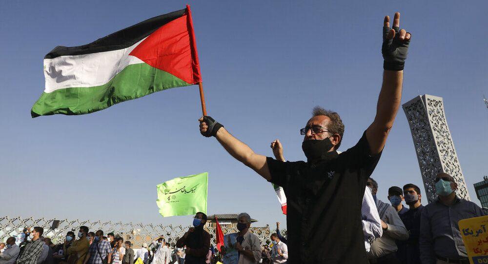 Manifestante segura bandeira palestina enquanto faz sinal da vitória em Teerã, Irã