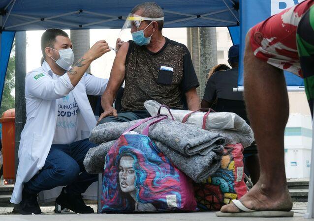 Funcionário de saúde aplica dose da vacina AstraZeneca durante campanha para imunização de população de rua no Rio de Janeiro
