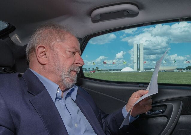 Ex-presidente Luiz Inácio Lula da Silva lê dentro de carro passando em frente ao Congresso Nacional, em Brasília