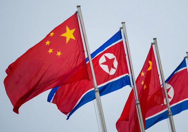 Bandeiras norte-coreanas e chinesas tremulam em Pyongyang em 19 de junho de 2019